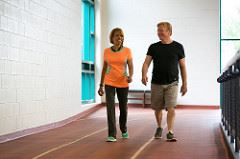 Two individuals walk on an indoor track